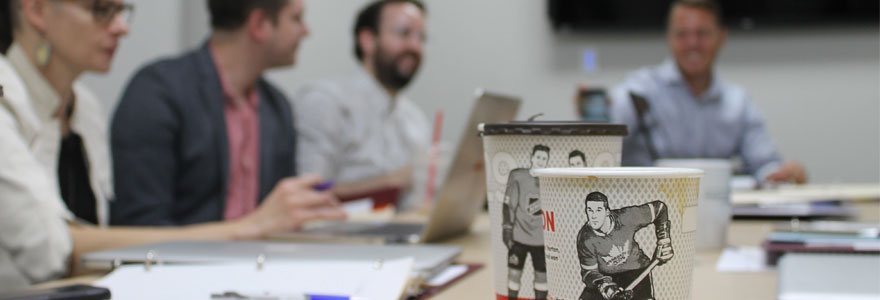 Coffee cups featuring hockey players, in foreground; researchers in backgroud